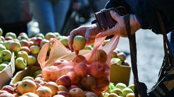 Женщина у прилавка с яблоками на сельскохозяйственной ярмарке в Ялте