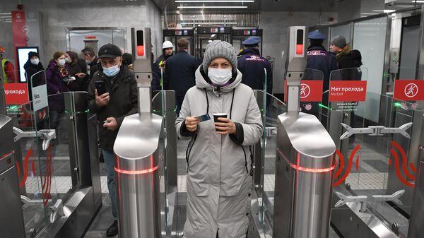 Пассажиры проходят через турникеты на станции Народное ополчение Большой кольцевой линии московского метрополитена