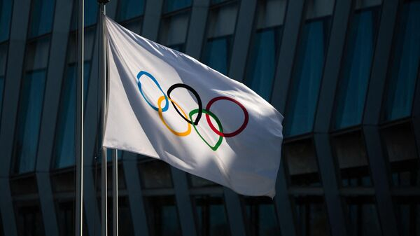 A picture taken on March 8, 2021 in Lausanne shows the Olympic flag floating next to the headquarters of the International Olympic Committee (IOC) ahead of a session of the World's sport governing body held virtually. (Photo by Fabrice COFFRINI / AFP)