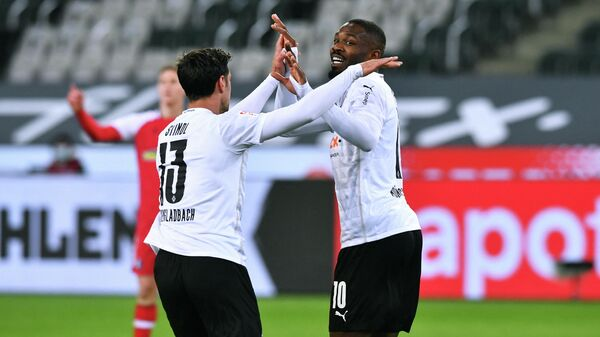Moenchengladbach's French forward Marcus Thuram celebrates after scoring together with his teammates Moenchengladbach's German forward Lars Stindl (L) during the German first division Bundesliga football match between Borussia Moenchengladbach and SC Freiburg in Moenchengladbach, western Germany, on April 3, 2021. (Photo by UWE KRAFT / AFP) / DFL REGULATIONS PROHIBIT ANY USE OF PHOTOGRAPHS AS IMAGE SEQUENCES AND/OR QUASI-VIDEO