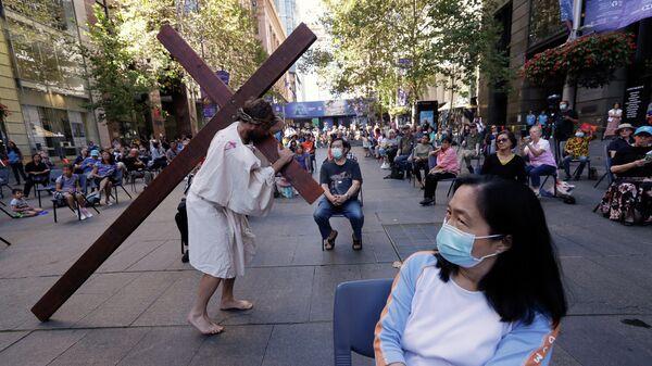 Актер несет крест, изображения Иисуса Христа во время празднования Страстной пятницы в Сиднее