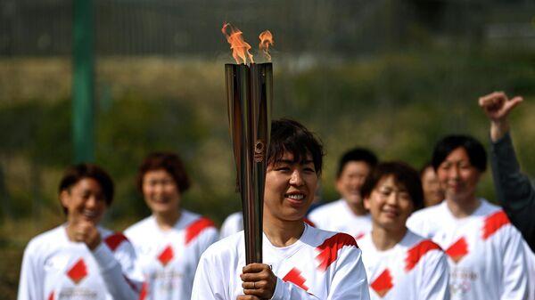 Японский факелоносец Азуса Ивашимицу во время эстафеты Олимпийского огня в Токио