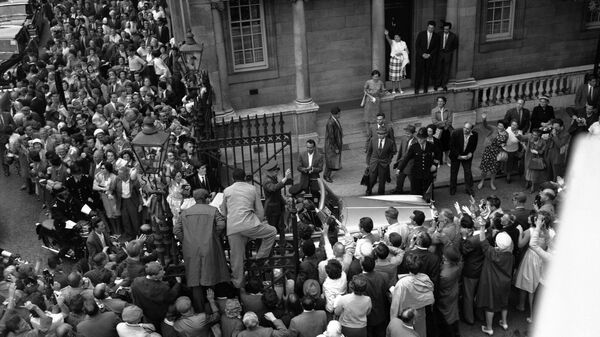 Люди залезают на ворота у советского посольства в Лондоне, 11 июля 1961 года, чтобы лучше разглядеть российского космонавта Юрия Гагарина, который стоит в открытом Rolls-Royce. Он приехал в Лондон на советскую выставку
