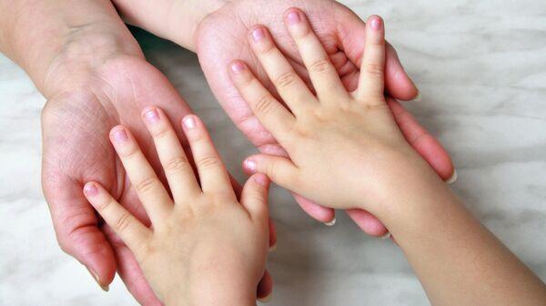 Ребенок держит за руки взрослого