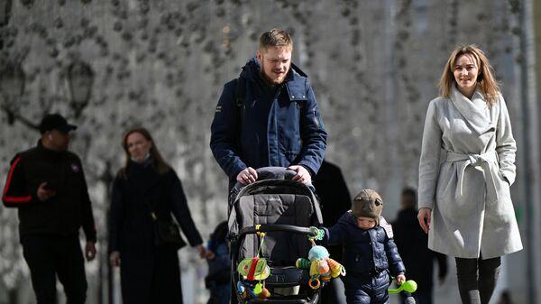 Молодые люди с ребёнком во время прогулки на улице Никольская в Москве