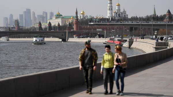 Прохожие на Москворецкой набережной и теплоходы на Москве-реке