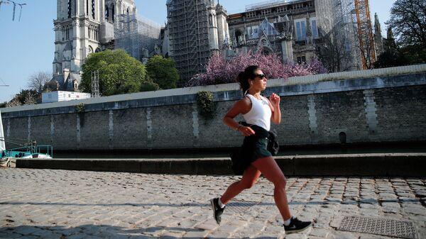 Женщина на пробежке перед собором Парижской Богоматери