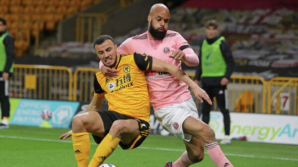 Wolverhampton Wanderers' Moroccan midfielder Romain Saiss (L) vies with Sheffield United's English-born Irish striker David McGoldrick (R) during the English Premier League football match between Wolverhampton Wanderers and Sheffield United at the Molineux stadium in Wolverhampton, central England on April 17, 2021. (Photo by Geoff Caddick / POOL / AFP) / RESTRICTED TO EDITORIAL USE. No use with unauthorized audio, video, data, fixture lists, club/league logos or 'live' services. Online in-match use limited to 120 images. An additional 40 images may be used in extra time. No video emulation. Social media in-match use limited to 120 images. An additional 40 images may be used in extra time. No use in betting publications, games or single club/league/player publications. /