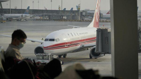 Пассажир ждет рейса в Международном аэропорту Пекин Дасин