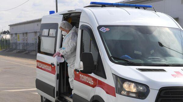 Медицинский работник выходит из салона скорой медицинской помощи