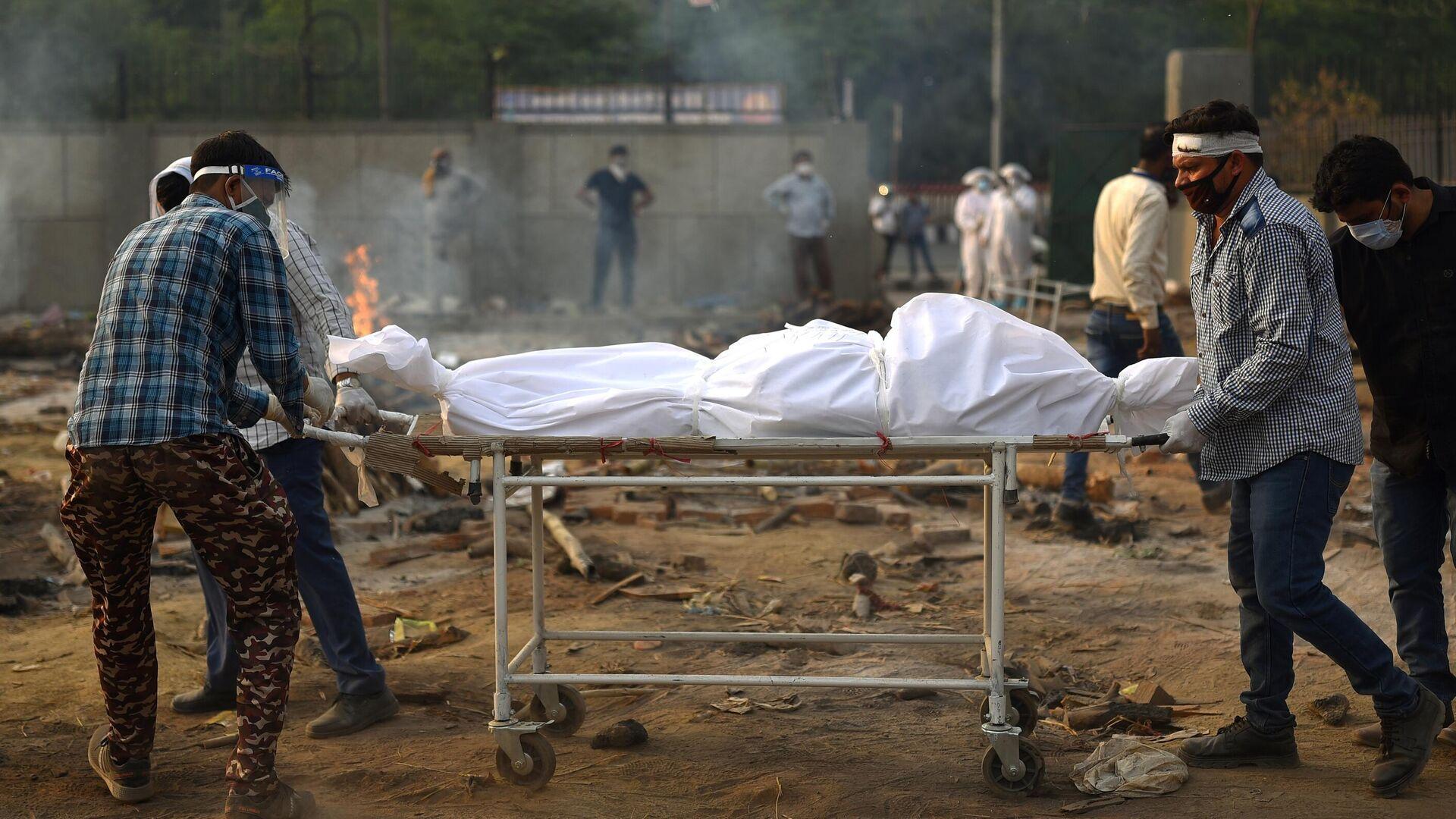 Подготовка тела погибшего к кремации жертв пандемии в Дели - РИА Новости, 1920, 12.05.2021