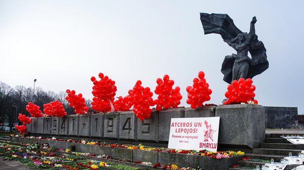 Воздушные шары и цветы у памятника Освободителям в Парке Победы в Риге в День Победы