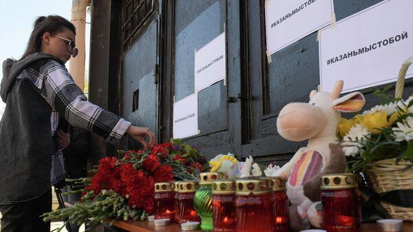 Девушка возлагает цветы в память о жертвах трагедии в казанской школе у здания Постоянного Представительства Республики Татарстан в Санкт-Петербурге