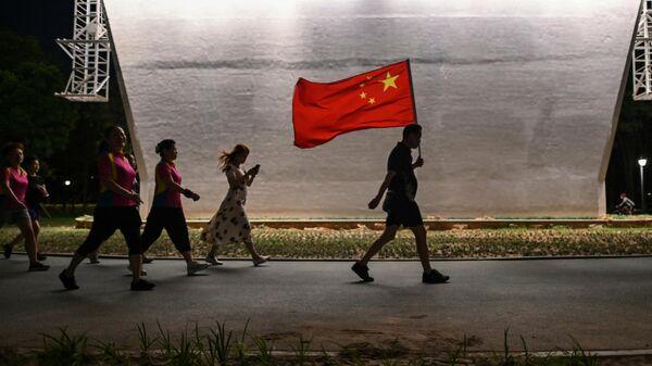 Мужчина с флагом Китая идет по парку в Ухани