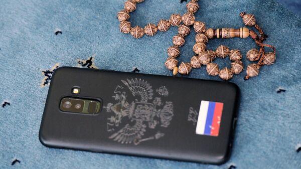 Мобильный телефон и четки на полу во время праздничной молитвы в честь Ураза-байрама возле мечети Кул Шариф в Казани