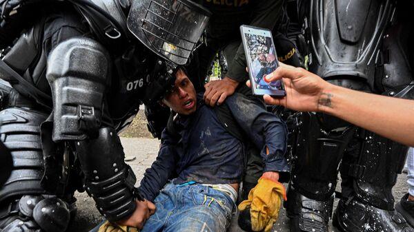 Колумбийские полицейские арестовывают демонстранта во время акции протеста против правительства в Кали, Колумбия