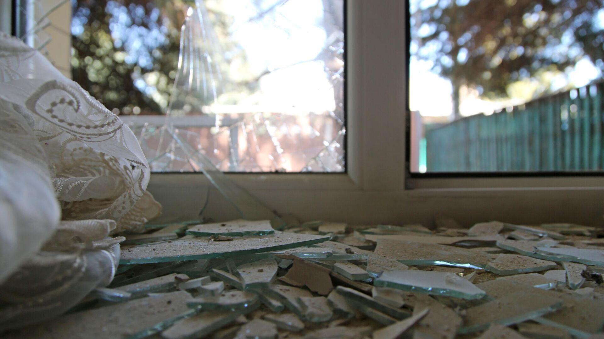 Разбитое окно дома, поврежденное разрывом снаряда в результате обстрела в Петровском районе Донецка - РИА Новости, 1920, 21.06.2021