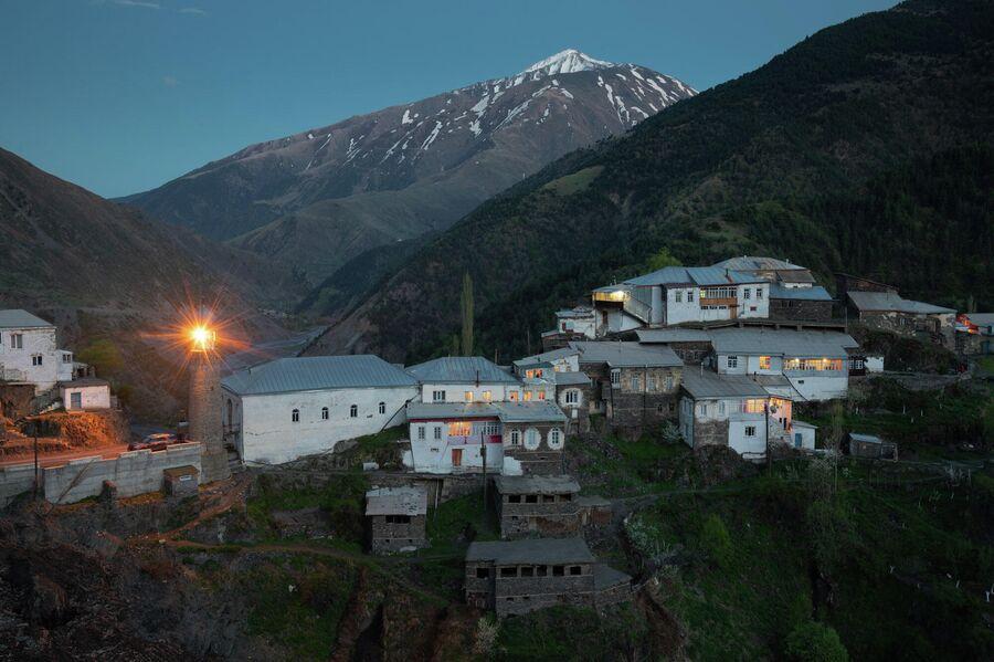 Село Цахур в закатных сумерках, южный Дагестан. Бело здание медресе (мусульманское училище) справа от минарета, основанное в 1075 году, является самым древнем медресе в России