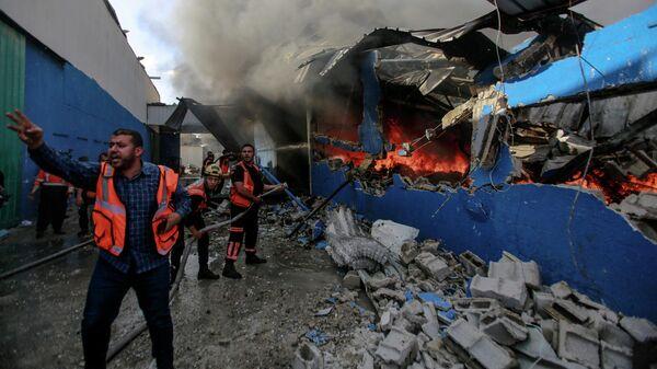 Члены Палестинской гражданской обороны тушат пожар на заводе по производству пенопласта в секторе Газа