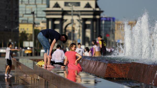 Молодые люди у фонтана в парке Победы в Москве в жаркую погоду