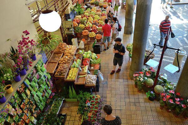 Лотки с фруктами на муниципальном фермерском рынке Меркадо дош Лаврадореш в городе Фуншал на острове Мадейр