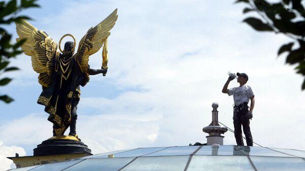 Рабочий на куполе здания возле памятника Архангелу Михаилу, Киев