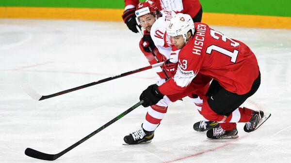 Слева направо: Сергей Толчинский (Россия) и Нико Хишир (Швейцария) в матче группового этапа чемпионата мира по хоккею 2021 между сборными командами Швейцарии и России.