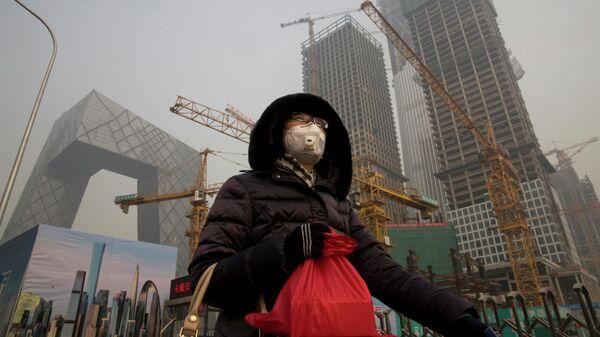 Девушка в защитной маске в Пекине на фоне строящихся зданий