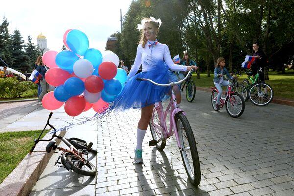 Участница праздничных мероприятий, приуроченных к празднованию Дня государственного флага Российской Федерации, в парке Победы на Поклонной горе в Москве