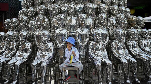 Мальчик на фоне инсталляции в Пекине, Китай