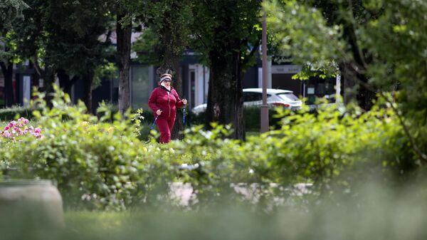 Женщина занимается скандинавской ходьбой на улице Красной в Краснодаре