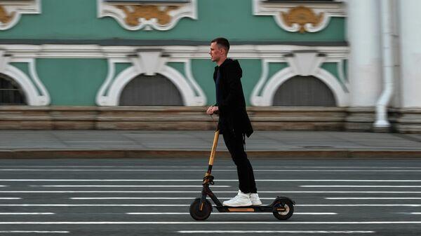 Молодой человек едет на самокате по Дворцовой площади в Санкт-Петербурге