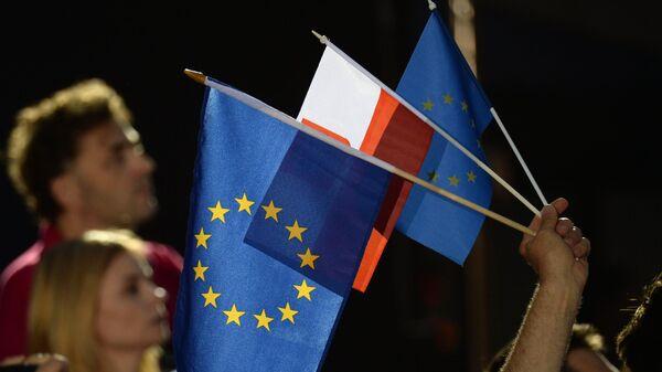 Люди с флагами Евросоюза и Польши в Варшаве