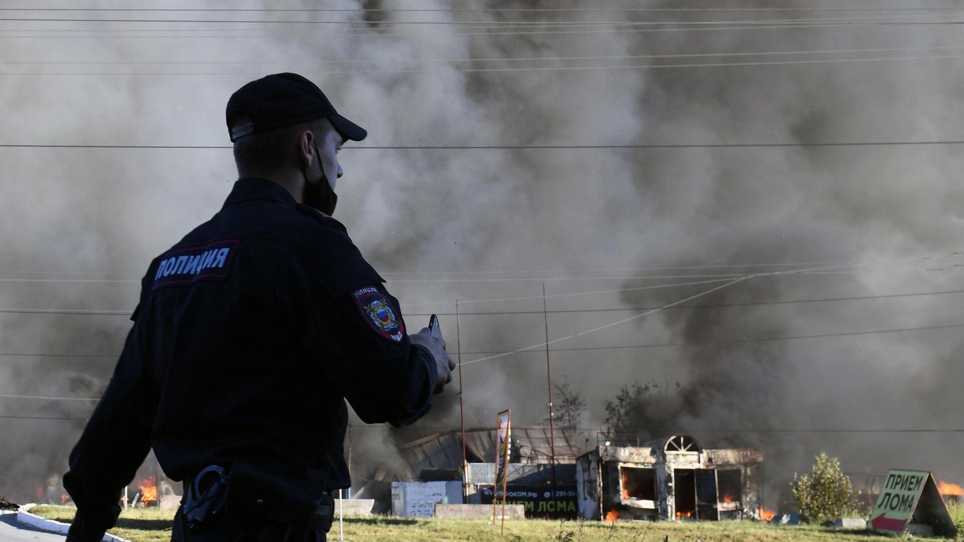 Сотрудник полиции у горящей автозаправки в Новосибирске - РИА Новости, 1920, 14.06.2021