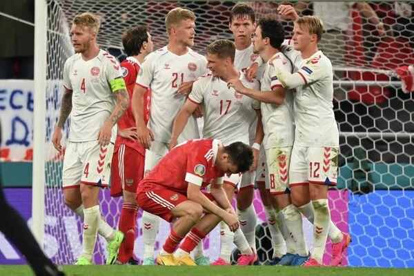 Полузащитник сборной России Александр Головин (на первом плане) и футболисты сборной Дании