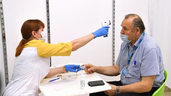 Медицинский работник измеряет температуру мужчине перед вакцинацией