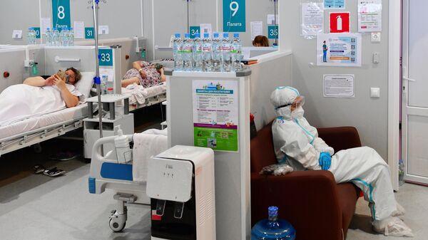 Медицинский работник и пациенты во временном госпитале для пациентов с COVID-19 в конгрессно-выставочном центре Сокольники в Москве