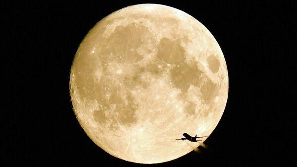 Летящий самолет на фоне полной Луны