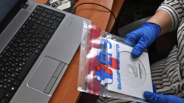 Учитель держит конверт с диском, в котором содержатся задания для ЕГЭ, перед началом единого государственного экзамена по информатике