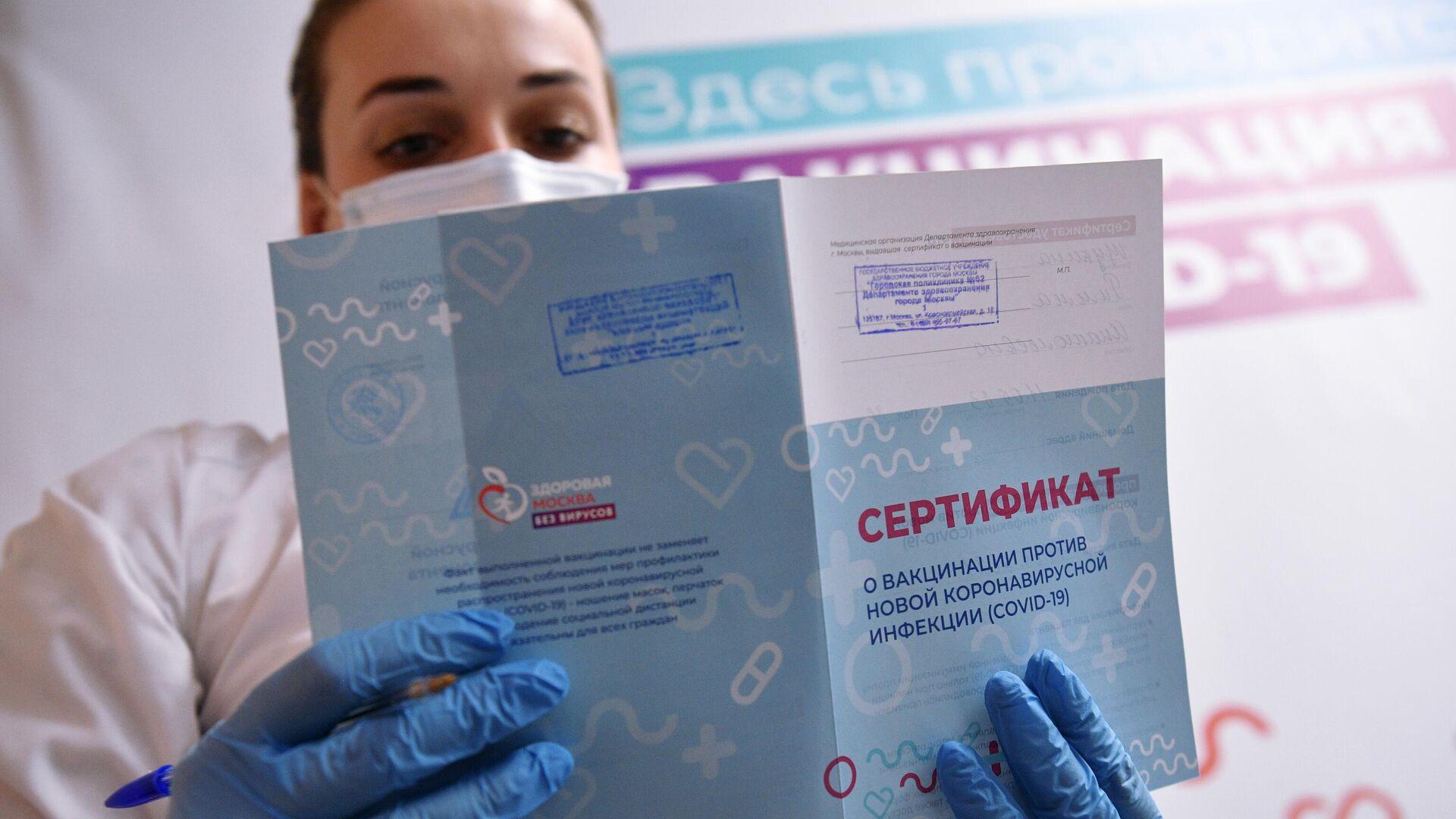 Медицинский работник держит в руках сертификат о вакцинации в мобильном пункте вакцинации от COVID-19 в торговом центре Арена Плаза в Москве - РИА Новости, 1920, 01.07.2021
