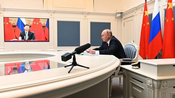 Президент РФ Владимир Путин и председатель КНР Си Цзиньпин во время беседы в формате видеоконференции