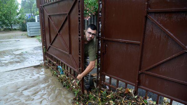 Мужчина убирается во дворе своего подтопленного дома в Хостинском районе Сочи