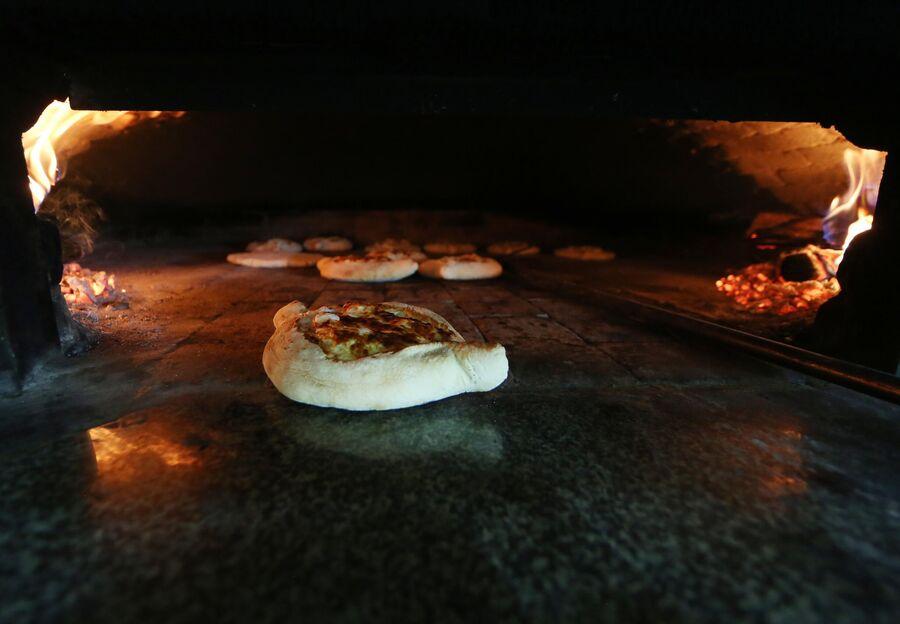 Выпечка в печи хачапури по аджарски в кафе города Батуми