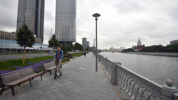 Мужчина катается на электросамокате на Пресненской набережной
