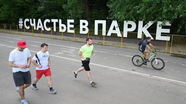 Люди возле арт-объекта Счастье в парке на Воробьевской набережной в Москве