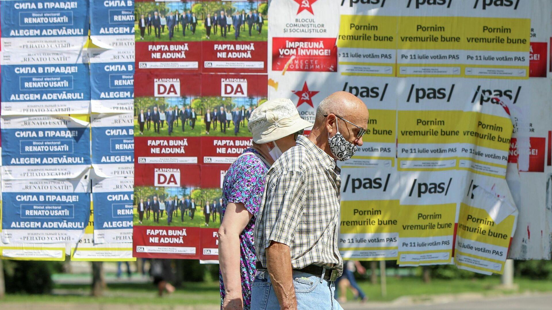 Люди проходят мимо избирательных плакатов накануне досрочных парламентских выборов в Кишиневе - РИА Новости, 1920, 11.07.2021