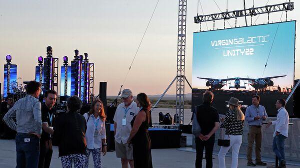 Гости собираются перед экраном, где будет проходить трансляция полета Ричарда Брэнсона на космическом корабле VSS Unity компании Virgin Galactic
