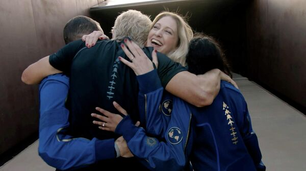 Главный астронавт-инструктор компании Virgin Galactic Бет Мозес обнимает Ричарда Брэнсона после завершения полета космического корабля VSS Unity