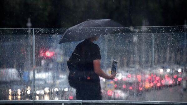 Мужчина под зонтом на одной из улиц в Москве