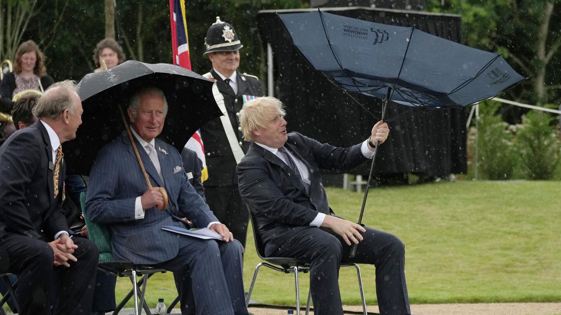 Британский принц Чарльз и премьер-министр Борис Джонсон укрываются от дождя во время открытия Мемориала полиции Великобритании в Национальном мемориальном дендрарии в Олревасе, Англия - РИА Новости, 1920, 31.07.2021